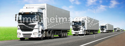 Caravan of white trucks on highway under blue sky