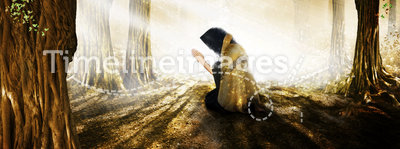 Prayer. A figure kneeling in the woods praying into a heavenly light. Concept for God is everywhere