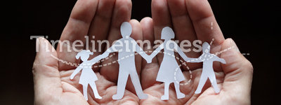 Paper chain family protected in cupped hands. Cutout paper chain family with the protection of cupped hands, concept for security and care