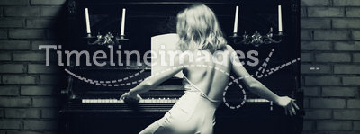Piano. Beautiful young woman playing the piano (black and white photo)