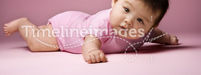 Baby lying on stomach looking at viewer.
