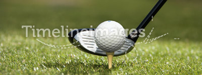 Golf club and golf ball on tee.