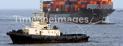 Container cargo ship with ocean tug