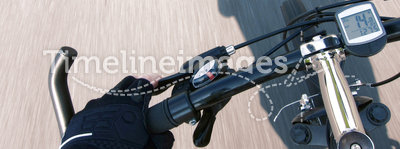 Cyclist Hand Glove on Speeding Bicycle Handlebar