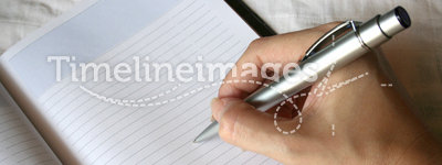 Hand holding pen writing on note book