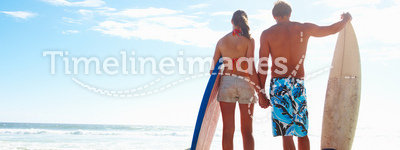Happy couple with surf boards by the sea