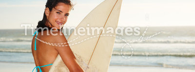 Happy female holding a surf board at the sea shore