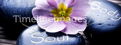 Wellness. Three massage stones - relax, body, soul - and a flower like a concept for wellness, reiki, body care and yoga symbols