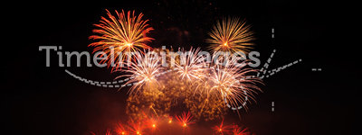 Red Fireworks. Multiple fireworks in a composition in shades of red, reflecting in water
