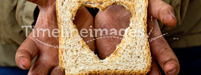 Help relief poverty and hunger with love. Poor kid dirty hands holding one slice of bread with love - poverty and hunger relief concept