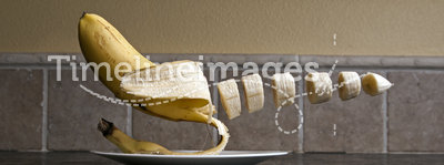 Floating Banana. Banana floating over a plate chopped up over a kitchen counter top