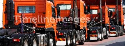 Line of heavy haulage orange trucks