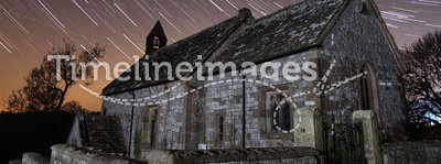 Old church at night with star trails