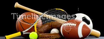 Sports Equipment. A variety of sports equipment on a black background including an american football, a soccer ball, a baseball, a baseball bat, a tennis raquet