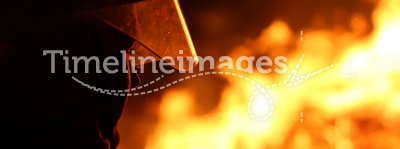 Firefighter. Silhouette of a firefighter facing a blazing fire