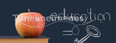Education = key - written on blackboard with apple
