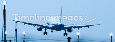 Landing. Airliner on final approach from back, about to touch down. Runway lights clearly visible. A blue toned image