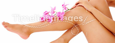 Woman with orchid branch over legs copyspace