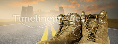 Worn work boots. A pair of worn work boots on an asphalt road going into a city in the far distant. Concept for hard work and building cities. Or concept for