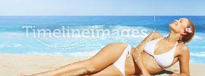 A pretty woman in bikini sunbathing at the beach