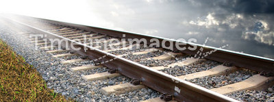 Railroad tracks. On a bed of rock on a grassy surface. Cloudy background with strong lighting to the left of the image. Concept for exploration or adventure