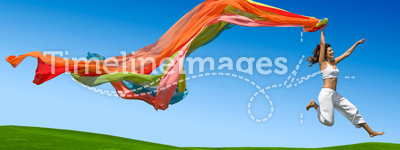 Rainbow woman. Young beautiful woman jumping with a colored scarf